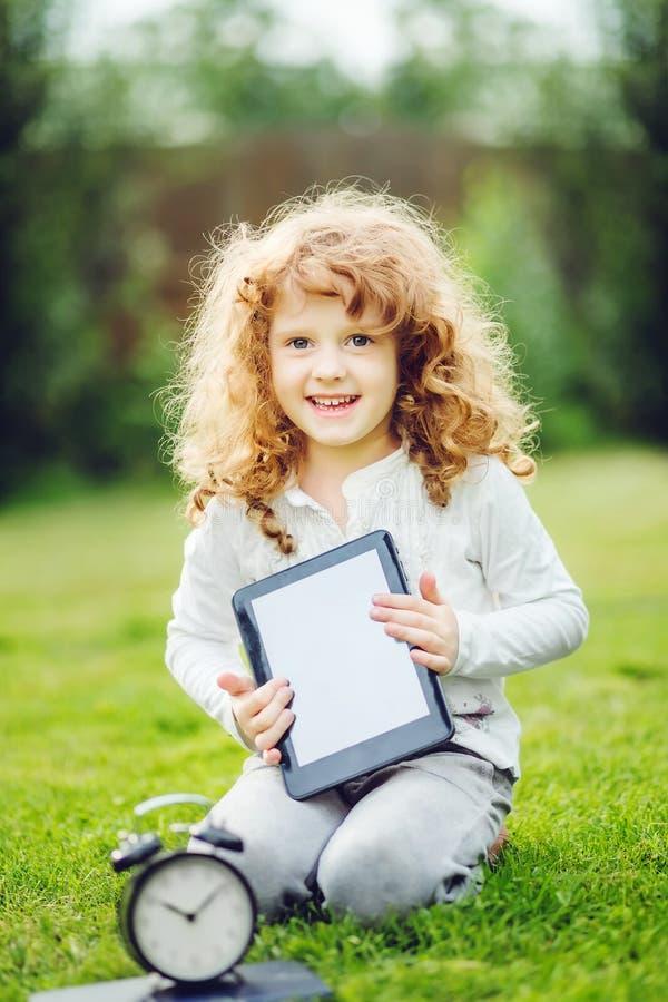 Niño feliz con el ordenador portátil que se sienta en la hierba fotos de archivo libres de regalías