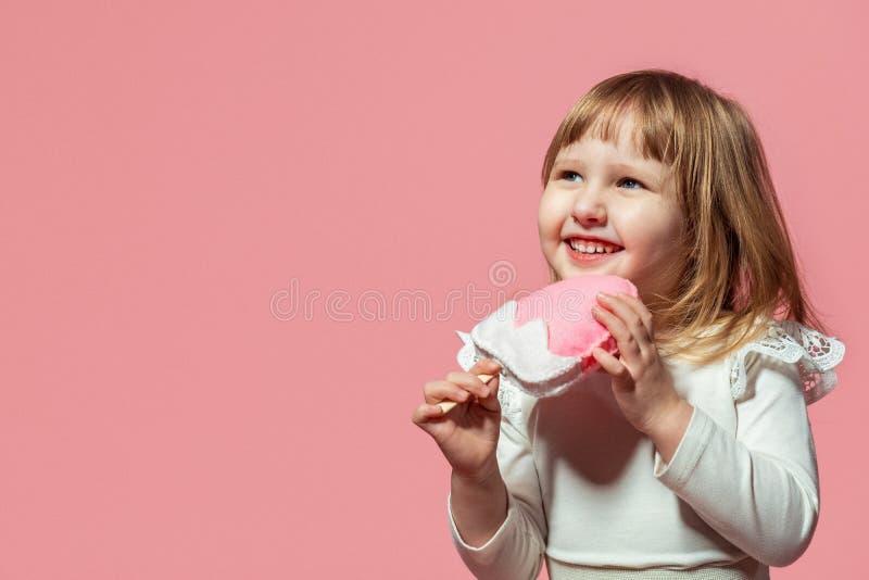 Niño feliz con helado del helado a disposición en un fondo coralino rosado fotografía de archivo libre de regalías