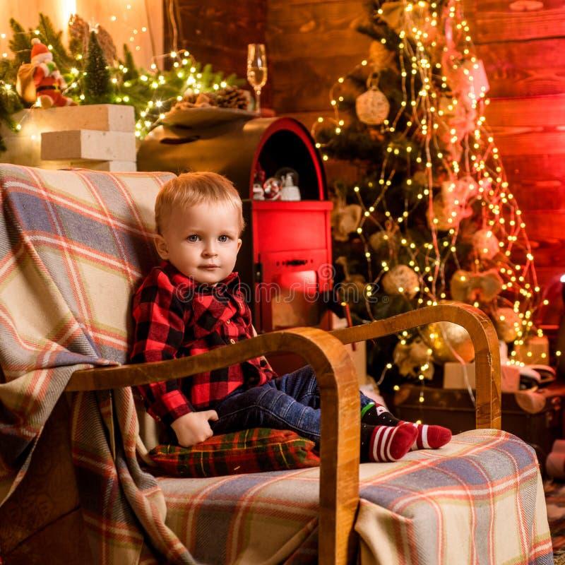 Niño feliz con humor de la Navidad Niño muy esperado El niño se está sentando en la mecedora y está mirando la cámara imagen de archivo libre de regalías
