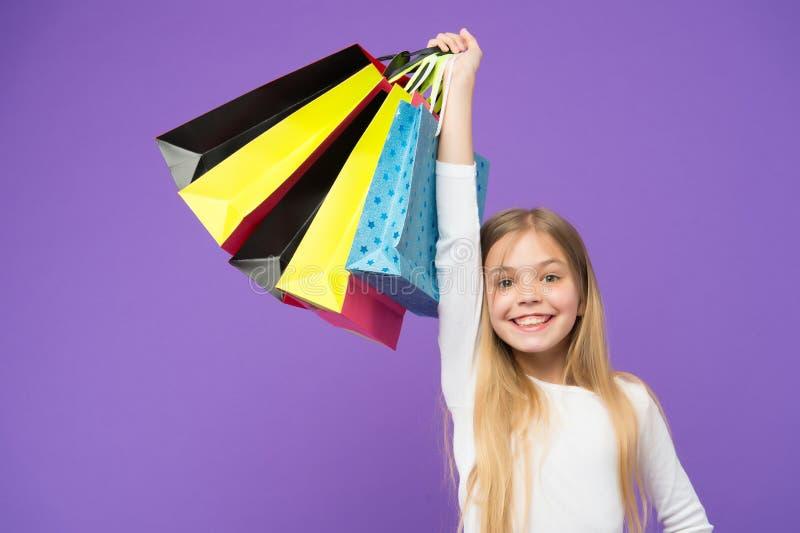Niño feliz con las bolsas de papel Sonrisa de la niña con los panieres en el fondo violeta Comprador del niño adentro en fondo pú fotografía de archivo libre de regalías