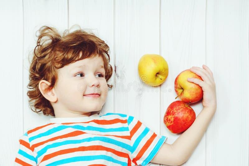 Niño feliz con las manzanas rojas en piso de madera ligero imagen de archivo