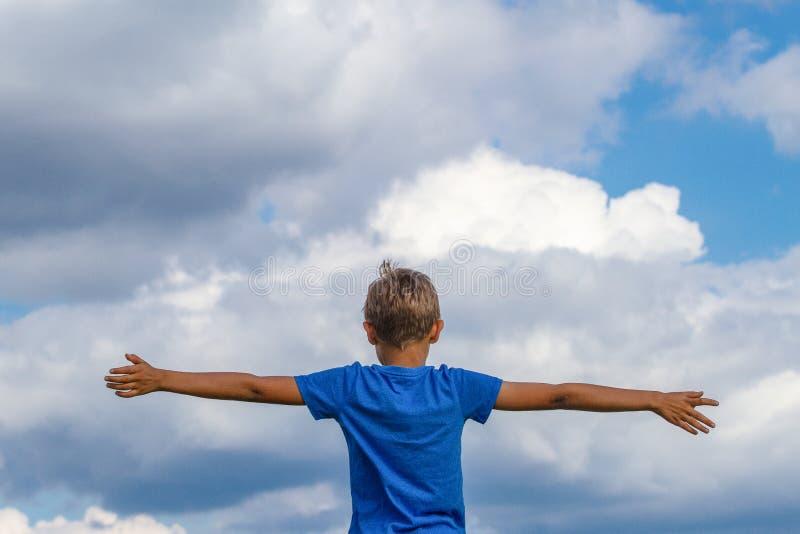 Niño feliz con los brazos aumentados contra el cielo azul Concepto de la libertad, de la alegría y de la felicidad fotografía de archivo libre de regalías