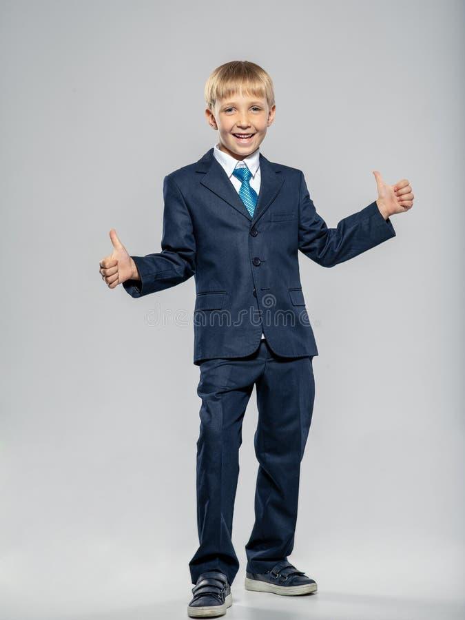 Niño feliz con traje de negocios azul con los pulgares arriba, posando en el estudio Chico alegre vestido con traje formal con co imagenes de archivo