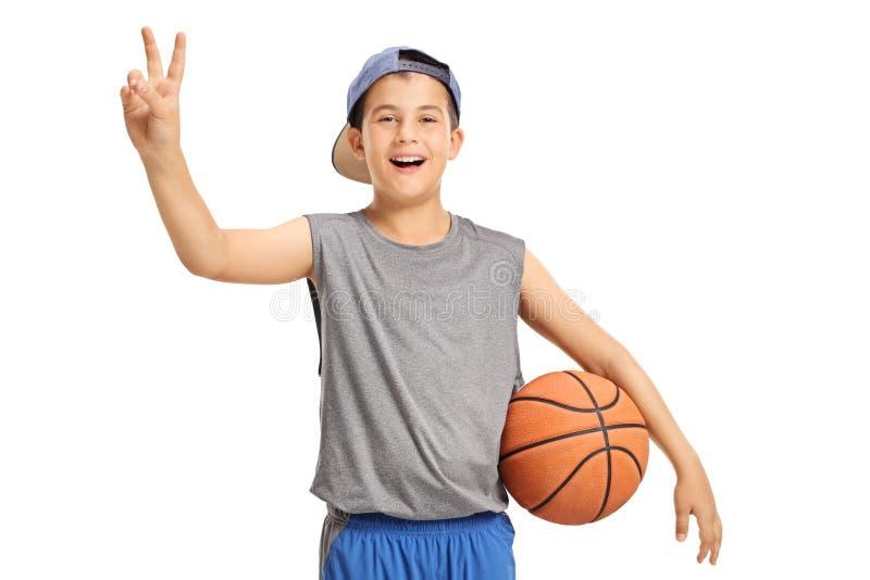 Niño feliz con un baloncesto que hace una muestra de la victoria imagen de archivo libre de regalías