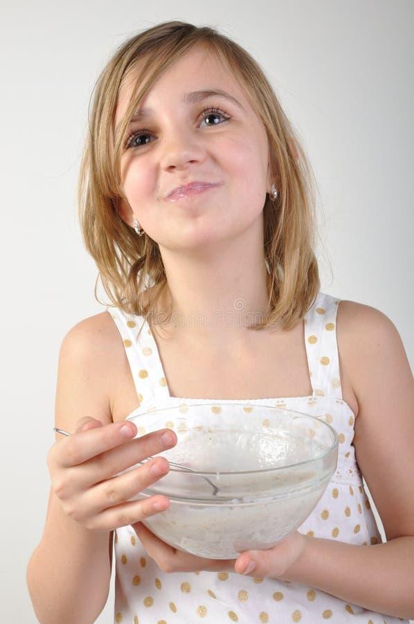 Niño feliz con un tazón de fuente de gachas de avena de la leche fotos de archivo
