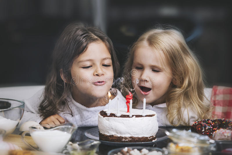 Niño feliz de dos niñas que celebra un cumpleaños con la torta en imagenes de archivo