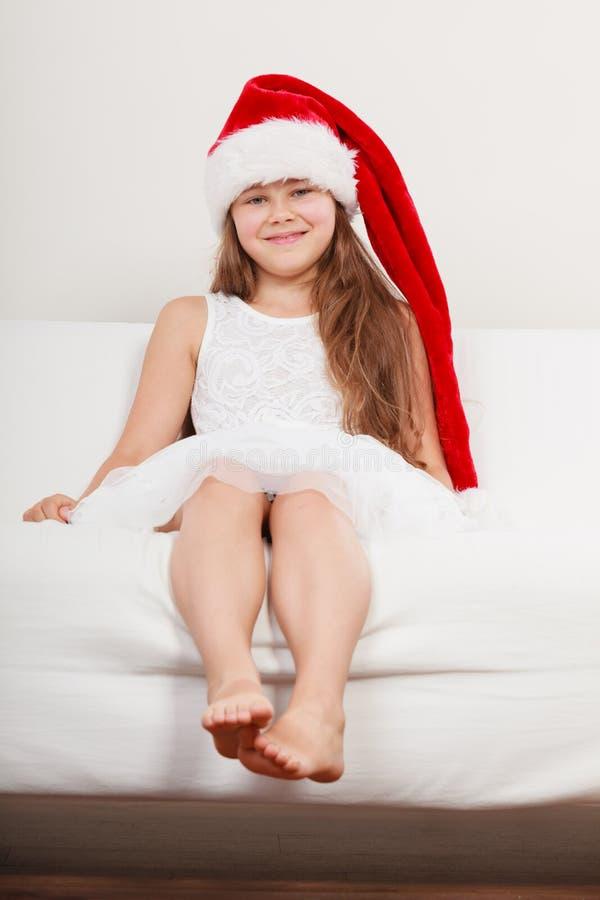 Niño feliz de la niña en el sombrero de santa Navidad imagen de archivo