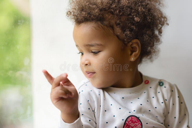 Niño feliz de la raza mixta cerca de la ventana imagen de archivo libre de regalías