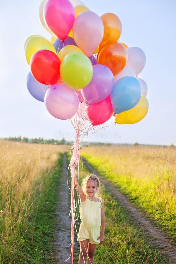 Niño feliz del niño de la niña con los globos en el campo imagenes de archivo