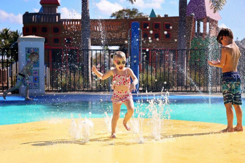 Niño feliz del niño que salta y que juega en fuentes de agua en el parque del chapoteo imagen de archivo libre de regalías