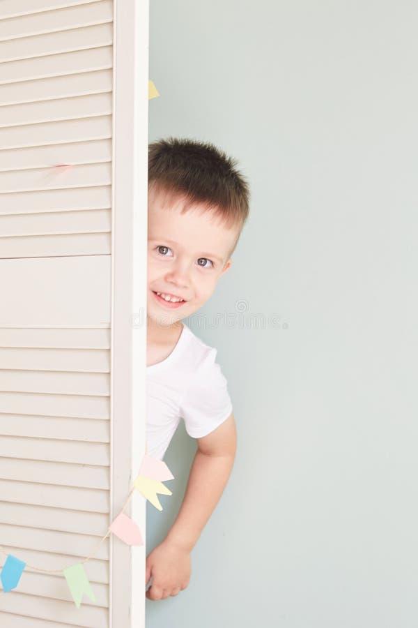Niño feliz detrás de la puerta los juegos del muchacho Él oculta detrás de la puerta blanca fotos de archivo