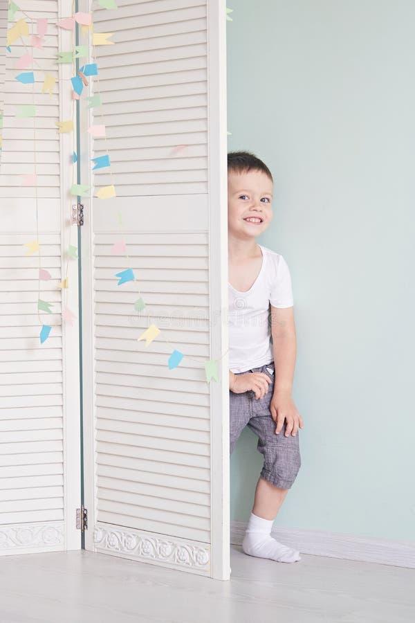 Niño feliz detrás de la puerta los juegos del muchacho Él oculta detrás de la puerta blanca fotografía de archivo libre de regalías