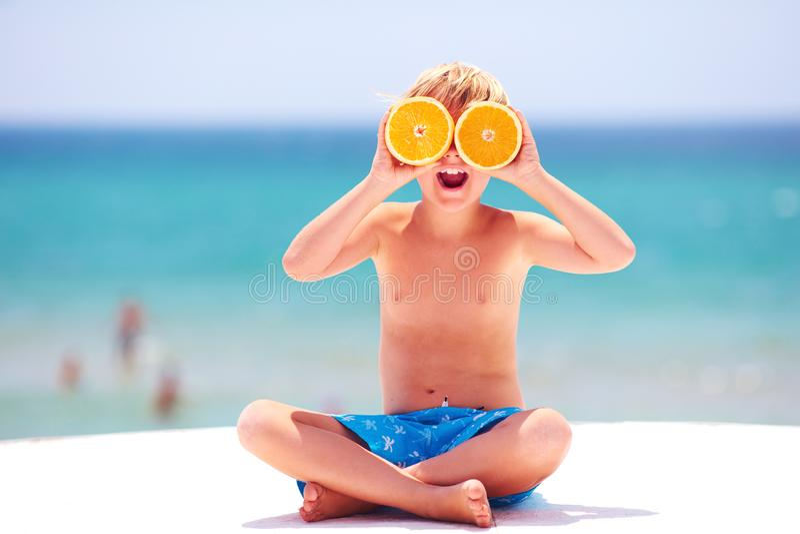 Niño feliz, emocionado, muchacho que se divierte en la playa, mostrando ojos anaranjados en las vacaciones de verano foto de archivo