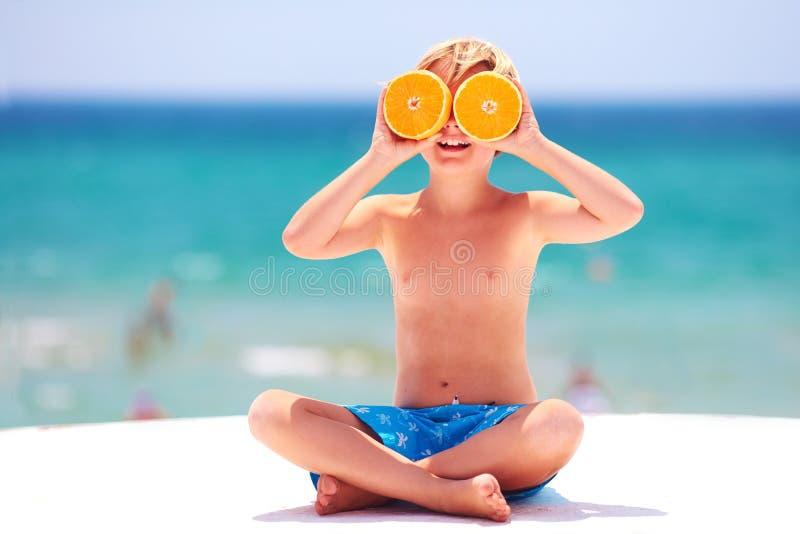 Niño feliz, emocionado, muchacho que se divierte en la playa, mostrando ojos anaranjados en las vacaciones de verano fotografía de archivo