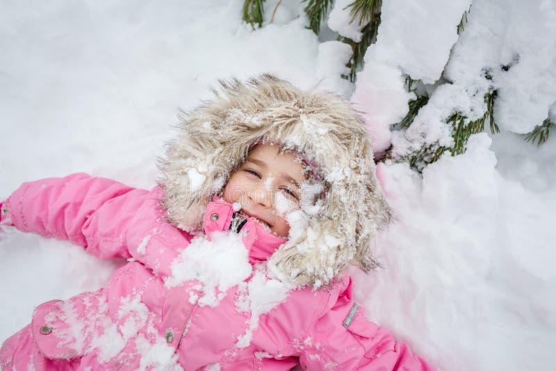 Niño feliz en bebé del bosque del invierno en una chaqueta rosada que miente en la nieve foto de archivo