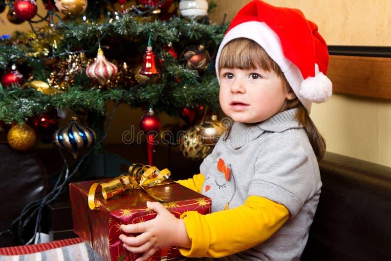 Niño feliz en caja de regalo de la Navidad de la abertura del sombrero de Papá Noel imagenes de archivo