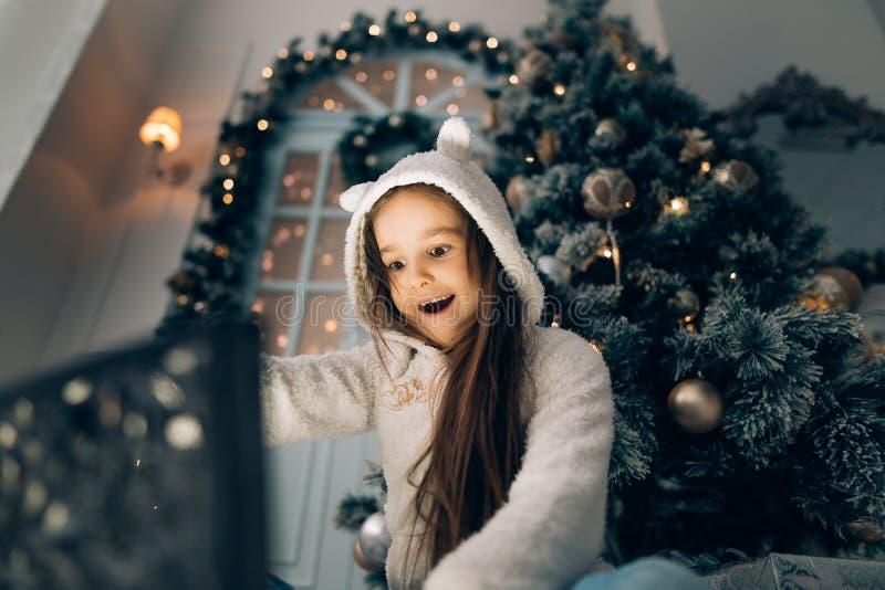 Niño feliz en caja de regalo de la Navidad de la abertura del sombrero de Papá Noel fotos de archivo