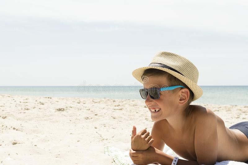Niño feliz en gafas de sol y sombrero en la playa Concepto de las vacaciones de verano imagen de archivo libre de regalías
