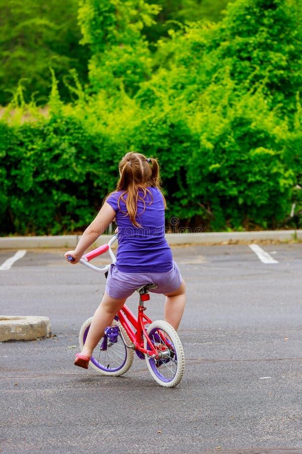 niño feliz en la chica joven de la bicicleta que monta su bicicleta en un día soleado fotos de archivo libres de regalías