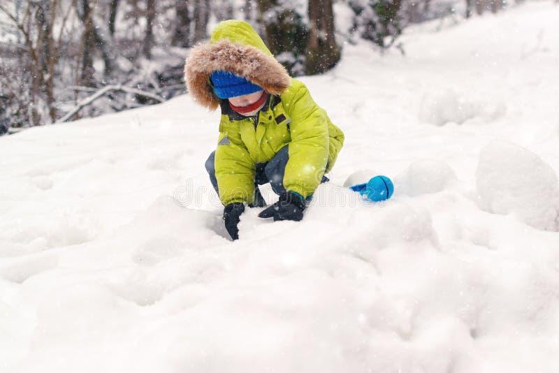 Niño feliz en la ropa caliente que juega con nieve Niño en ropa caliente en invierno Niño que hace bolas de nieve en día frío del foto de archivo libre de regalías