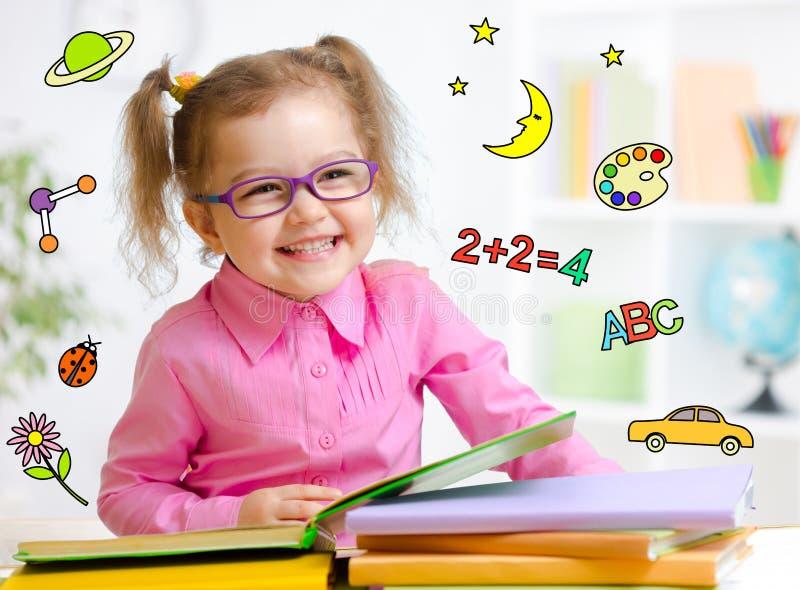 Niño feliz en libro de lectura de los vidrios temprano imagenes de archivo