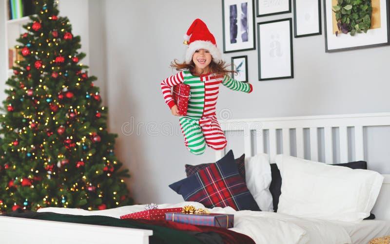 Niño feliz en pijamas con los regalos que saltan en cama en la Navidad m foto de archivo libre de regalías
