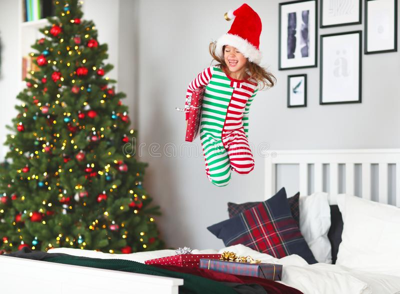 Niño feliz en pijamas con los regalos que saltan en cama en la Navidad m imagenes de archivo