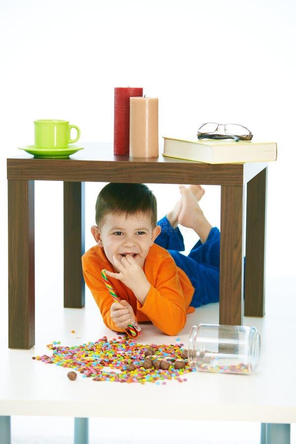 Niño feliz que come los dulces debajo de la tabla en casa imagen de archivo libre de regalías
