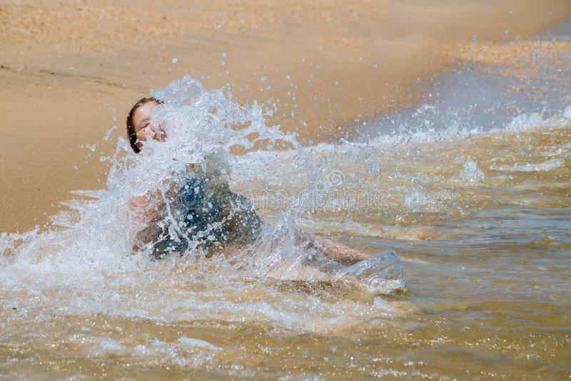 Niño feliz que corre en las ondas durante vacaciones de verano en la playa en la niña de la costa del océano que aprende nadar fotos de archivo