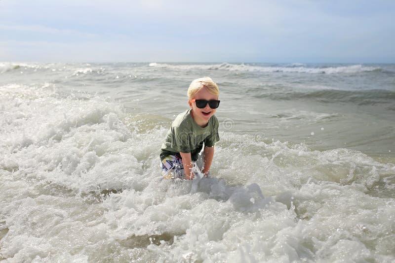 Niño feliz que juega afuera en las olas oceánicas fotografía de archivo