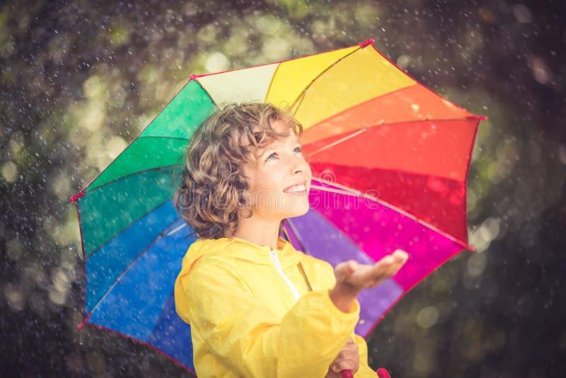 Niño feliz que juega bajo la lluvia fotos de archivo libres de regalías