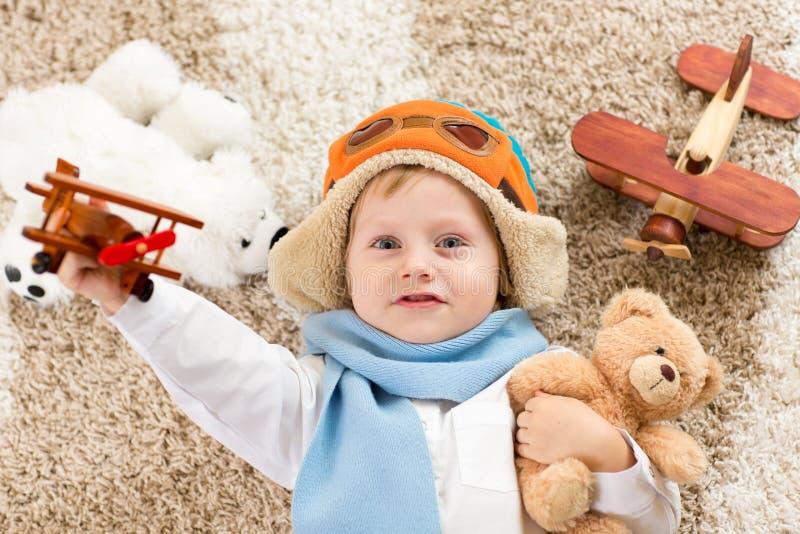 Niño feliz que juega con el aeroplano del juguete Muchacho del niño que miente en la alfombra mullida imágenes de archivo libres de regalías