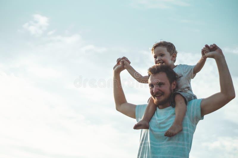 Niño feliz que juega con el padre Papá e hijo al aire libre Niño que lleva del padre en el suyo detrás Familia feliz en campo del foto de archivo