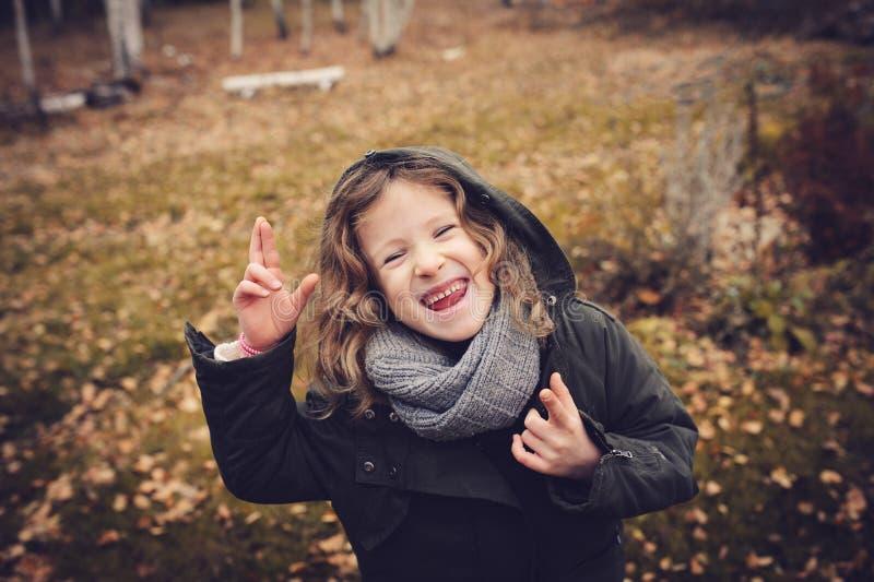 Niño feliz que juega con las hojas en otoño Actividades al aire libre estacionales con los niños fotos de archivo