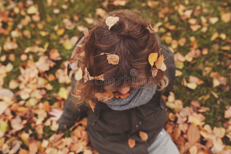 Niño feliz que juega con las hojas en otoño Actividades al aire libre estacionales con los niños imagen de archivo