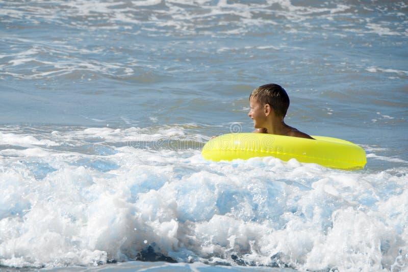 Niño feliz que juega en el agua azul del mar fotografía de archivo