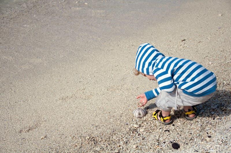 Niño feliz que juega en la playa de la arena imagen de archivo libre de regalías