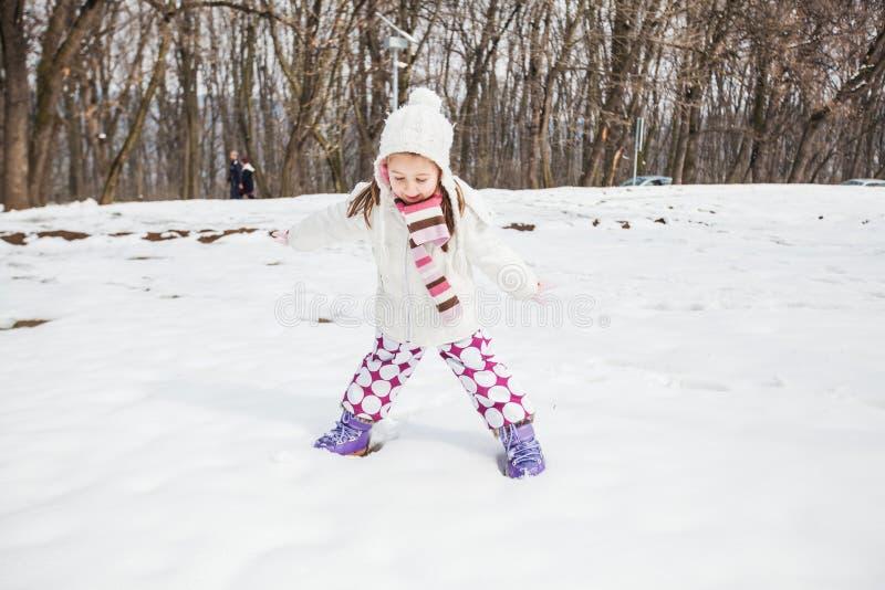 Niño feliz que juega en nieve en el parque en el día de invierno imagen de archivo libre de regalías