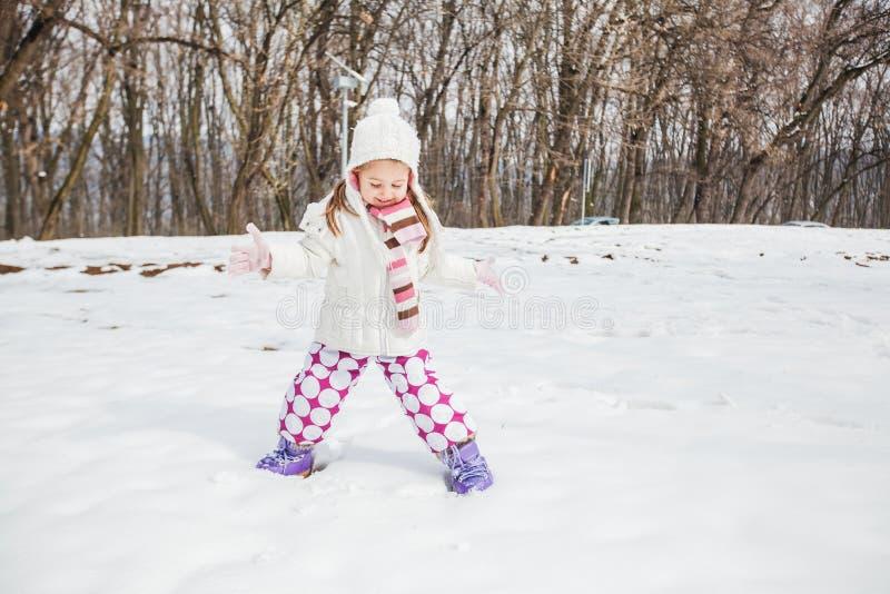 Niño feliz que juega en nieve en el parque en el día de invierno imagen de archivo