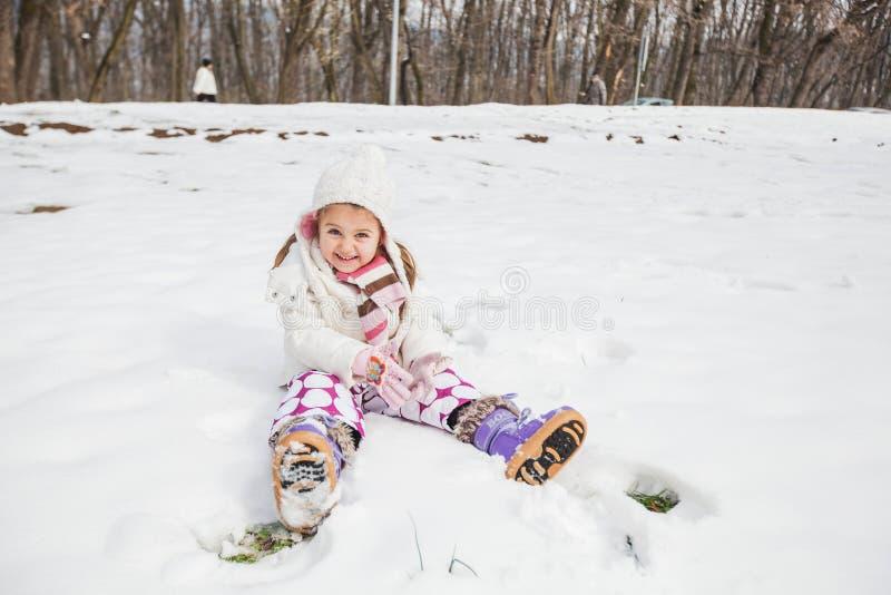 Niño feliz que juega en nieve en el parque en el día de invierno imagenes de archivo