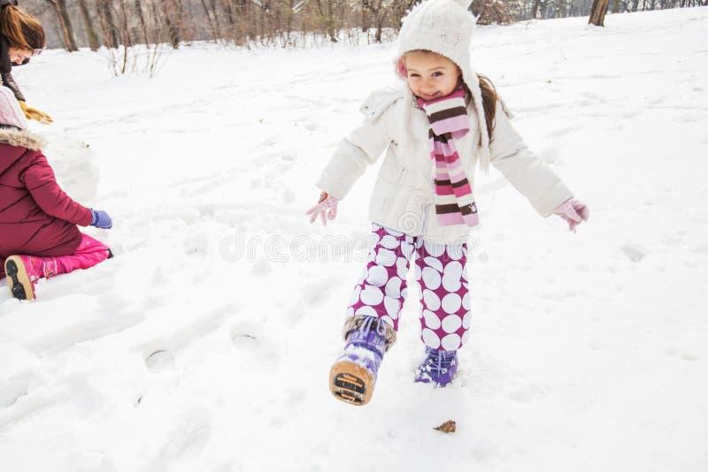 Niño feliz que juega en nieve en el parque en el día de invierno fotografía de archivo