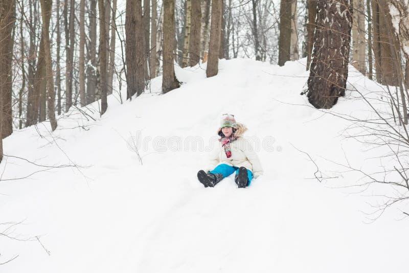 Niño feliz que monta abajo de una colina nevosa imagenes de archivo