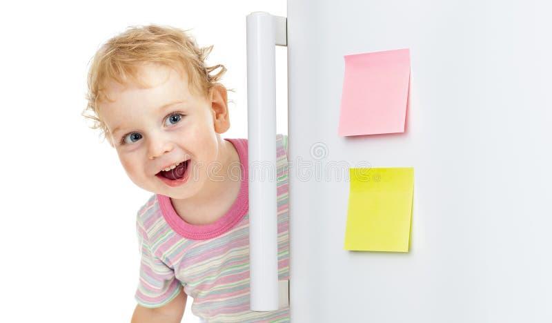 Niño feliz que oculta detrás de puerta del refrigerador imagenes de archivo