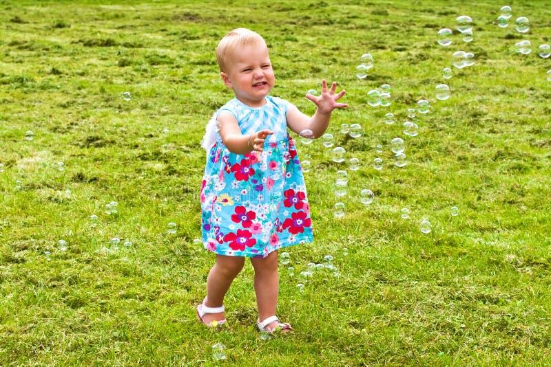 Niño feliz que persigue burbujas de jabón fotografía de archivo libre de regalías