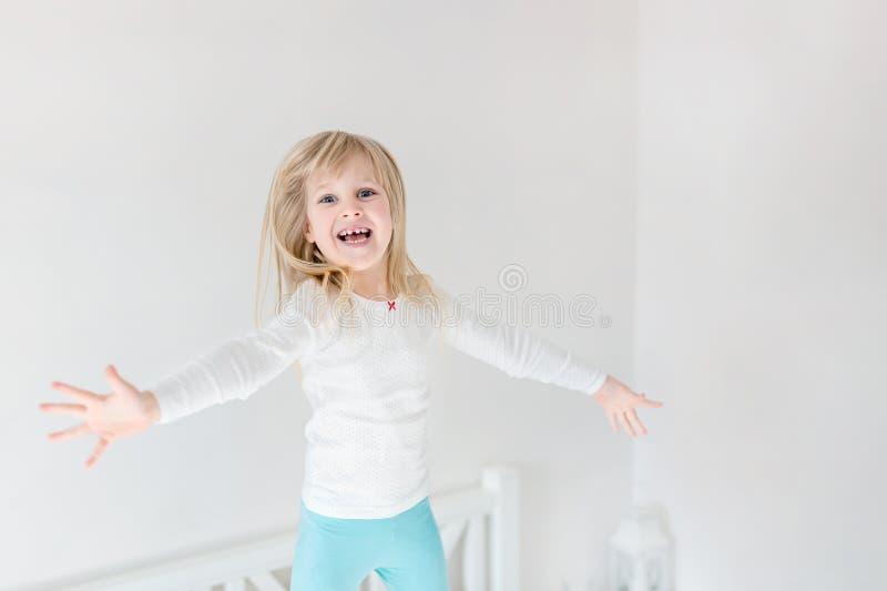 Niño feliz que salta sobre cama Pequeña muchacha rubia linda que se divierte dentro Concepto feliz y descuidado de la niñez fotografía de archivo libre de regalías