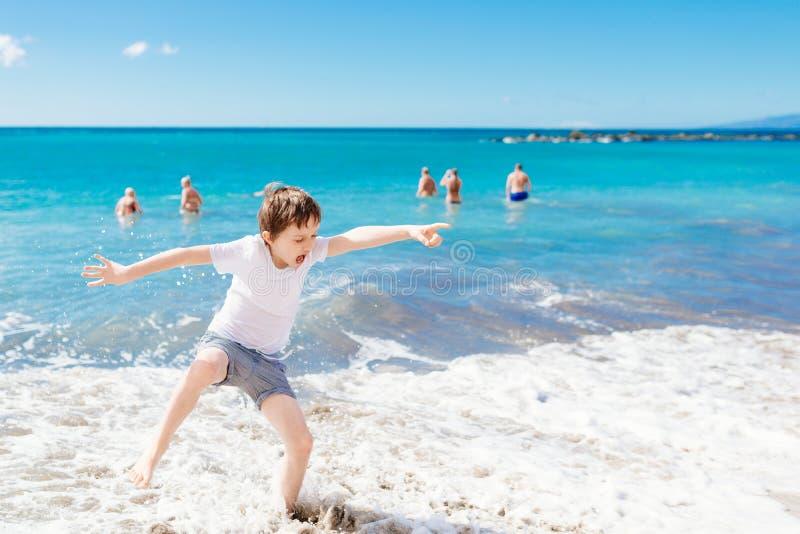 Niño feliz que salta y que juega en la playa imagen de archivo