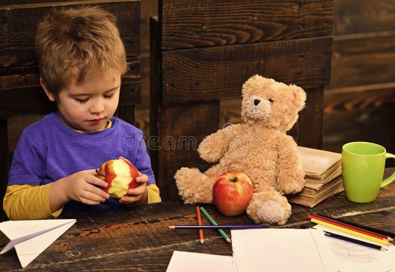 Niño feliz que se divierte Muchacho adorable que come la manzana deliciosa Niño que comparte el bocado con el juguete preferido A imagen de archivo