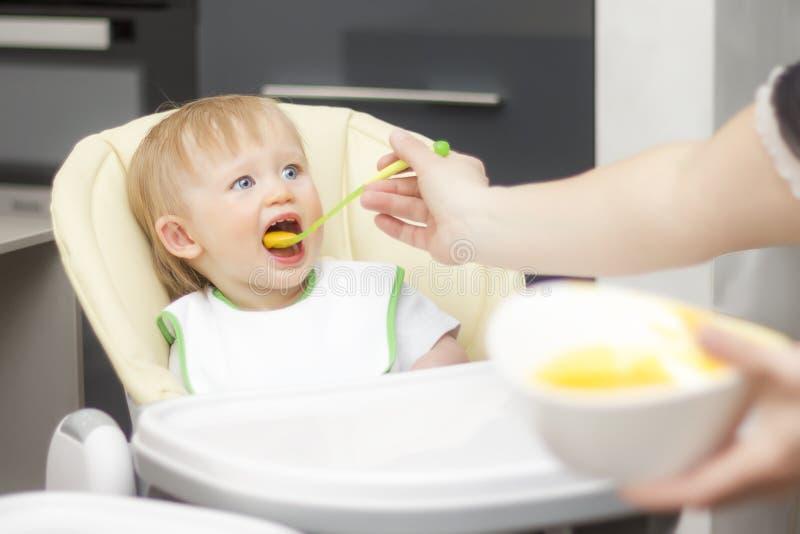 Niño feliz que se sienta en highchair y que come las gachas de avena El bebé que aprende comer y tiene yogur en las gachas de ave foto de archivo