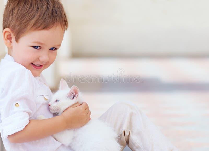 Niño feliz que sostiene el gato blanco lindo imagen de archivo