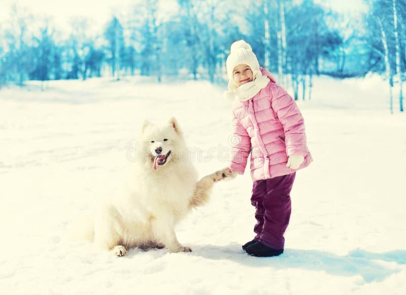 Niño feliz que sostiene el perro blanco del samoyedo de la pata en nieve en invierno foto de archivo